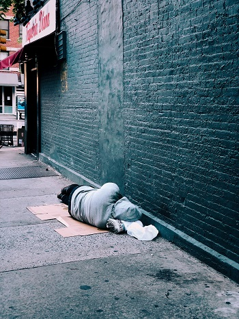 A homeless man lies alone on the street next to a bare brick wall.