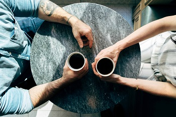 Looking down on a round table, two sets of arms hold coffee cups
