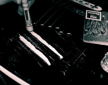 Lines of cocaine on a table with a rolled up bill being used to snort them.
