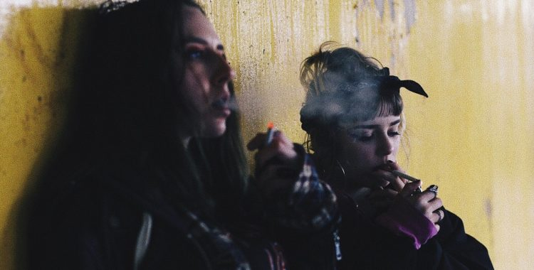 Two women sitting against a dirty wall smoke cigarettes