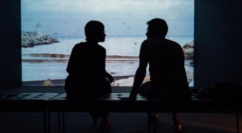 Two people sit talking in the dark, facing a window to a dreary landscape