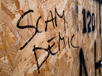 """An exposed particle board wall with """"SAMDEMIC"""" spray painted on it."""