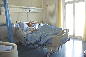 A woman lays in a hospital bed with her hand on her head, deep in thought.