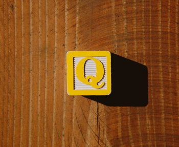 """A yellow child's letter block with the letter """"Q"""" on it."""