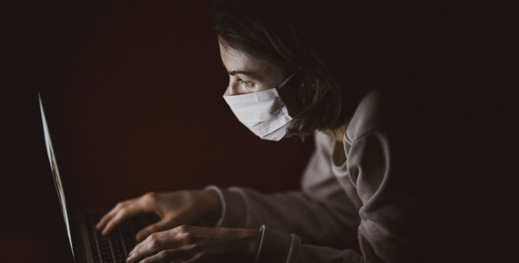 A woman in a surgical mask types on a laptop computer in a dark room.