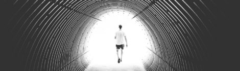 A person walks away, disappearing into a tunnel of white light.