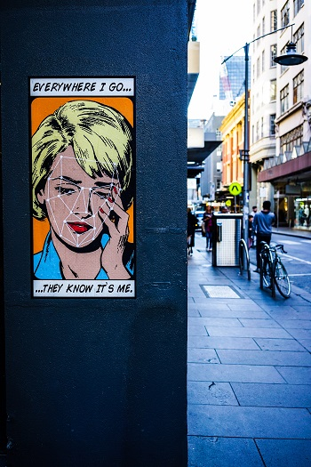 """A cartoon image of a crying woman is posted on a wall beside a street. Text reads """"Everywhere I go, they know it's me"""""""