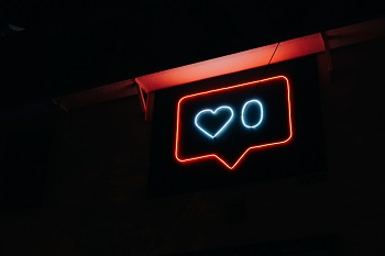 A neon sign displays an Instagram heart with zero likes