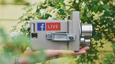 A video camcorder held in a hand with a Facebook logo on it.