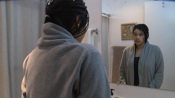 Still of Marshay looking in the mirror.