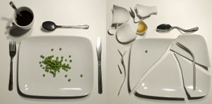 Two plates sit side by side, one with a few peas on it, the other broken into pieces.