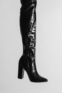 A long, high-heeled, black leather boot