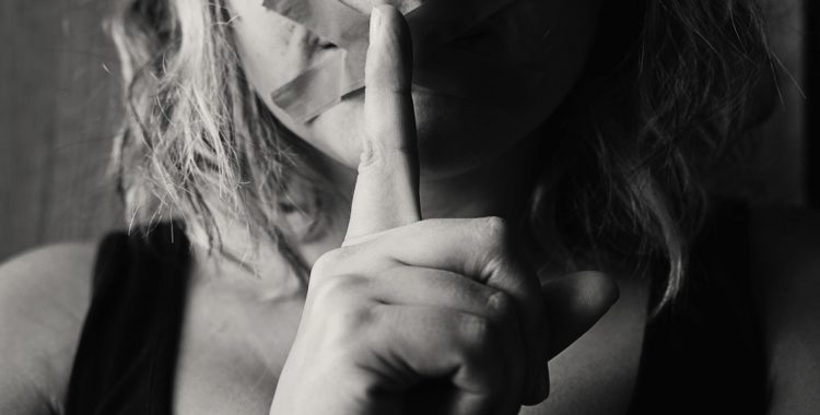 A woman holds a finger up to her tape covered mouth to indicate silence.