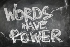 """Words written with white chalk on chalkboard that reads """"Words Have Power""""."""