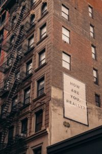 """Image on the side of a brick building that read """"How are you really?"""""""