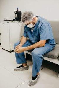 A male physician wearing scrubs, hairnet, and mask seated with hands clasped and looking down.