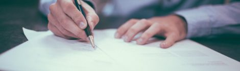 A man signing legal documents at a table with a pen.