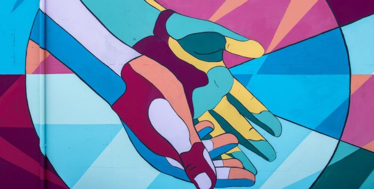 Abstract and multicolour painted image of open-palmed hands.