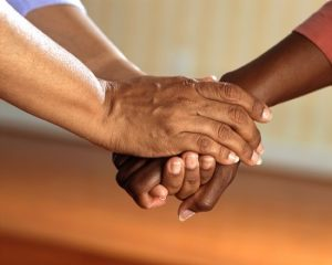 Two arms reach to each other, clasping hands