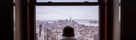 A man, facing away, stares out at a cityscape