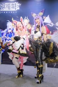 Two women cosplaying in a pink and purple wig and cosplay outfits.