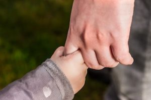 Small child's hand holding adult finger.