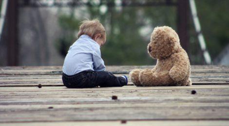 A small boy sitting with a teddy bear on a wooden bridge.