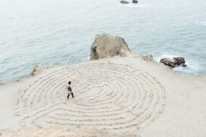 A person walking into the centre of a circular pattern etched out into the sand on a beach.