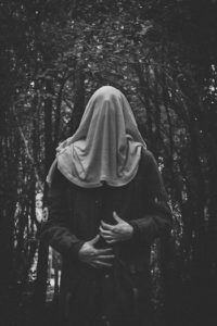Black and white image of a person with a cloth bag over their head, standing in a forest.