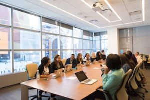 Women in a conference room, sitting around a long rectangular table.