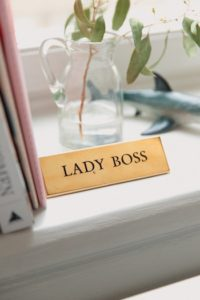 """Sign with """"LADY BOSS"""" written on it, sitting on a window sill."""