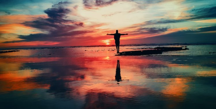 Person standing with their hands open on a beach with the water reflecting a colourful sky.