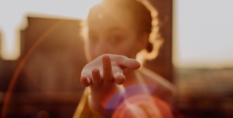 Dancer beckoning to the camera with her hand in the sunlight.