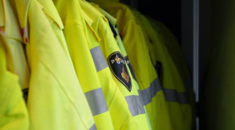 Yellow police jackets lined up and hanging on a clothing rack.