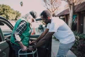 A volunteer helping an older man with a walker into a car.