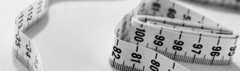 Loose measuring tape on a white surface.