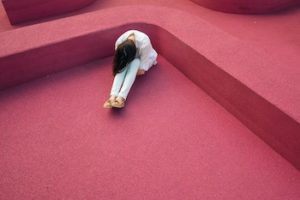 Woman sitting on red carpeted floor in a corner, bent over with her face in her knees.