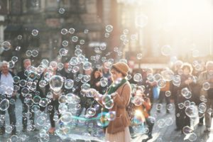 Woman smiling and holding her hands out, surrounded by bubbles.