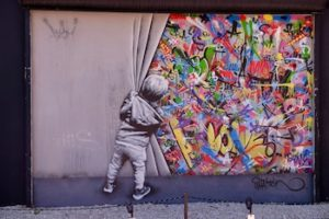 Graffiti on a cement wall depicting a black-and-white image of a child pulling back a curtain to reveal a colourful image behind.