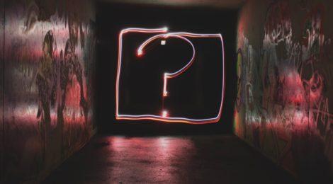Neon question mark in a dark room.