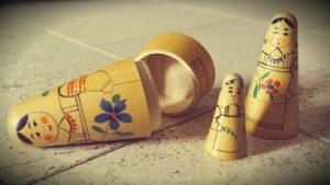 Three wooden Russian dolls on the ground, the largest one laying open on its side and subsequent smaller ones standing upright.