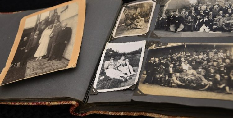 An old family photo album, open, revealing the yellowed and black-and-white photos within.
