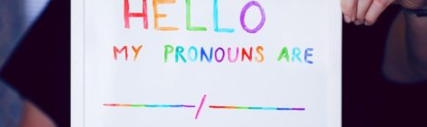 """Someone hold a small whiteboard, with the following written in mulit-colour marker: """"HELLO / MY PRONOUNS ARE _____/_____""""."""